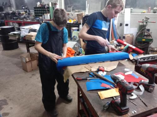 Team members busy building bumpers and developing upholstery skills.